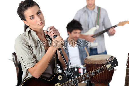 brunette singer with guitar and microphone