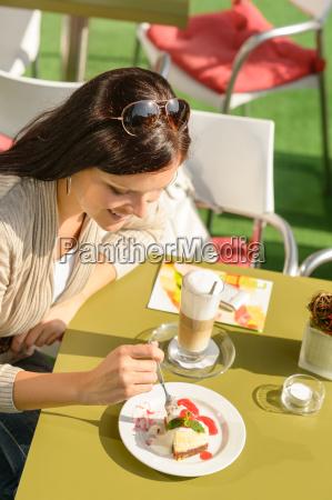 frau isst kaesekuchen im cafe bar
