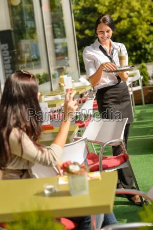 kellnerin bringt frau kaffee bestellen restaurant