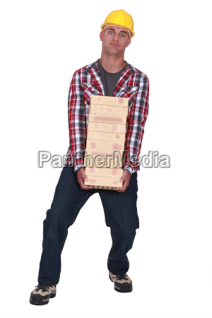 tradesman carrying a heavy load of
