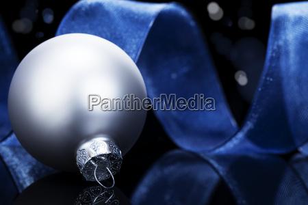 silberne christbaumkugel vor blauem band