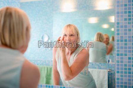 female beauty old woman applying cream