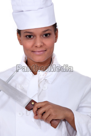 female chef sharpening a knife