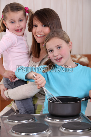 mother and two young daughters cooking