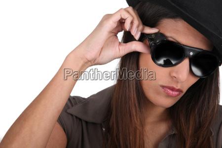 kuehle bruenette in sonnenbrille und hut