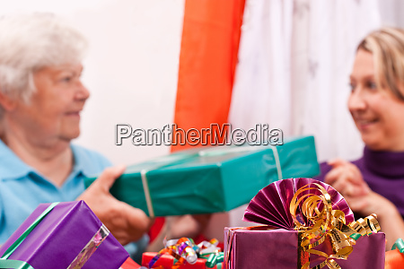 seniorin and young woman gift each