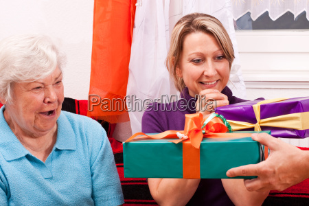 seniorin and young woman get gifts