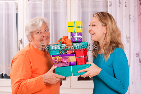 old and young woman holding many