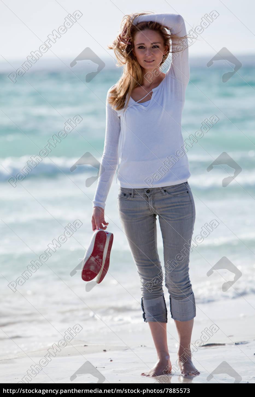 junge hübsche frau spaziert am strand im sand im
