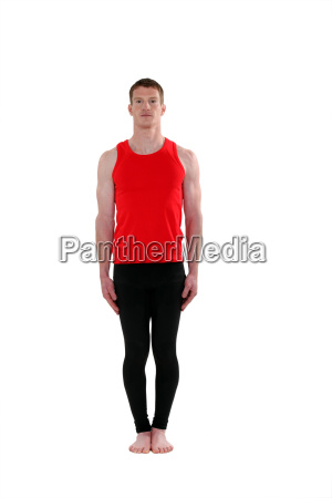 male gymnast standing upright against white
