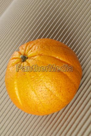 fresh orange on a corrugated cardboard