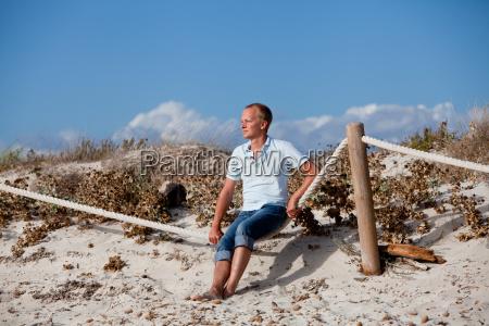 junger mann entspannt am strand in