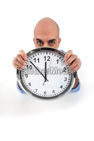 man holding a huge clock