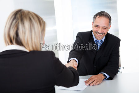 geschaeftsmann beim interview schuettelt die haende
