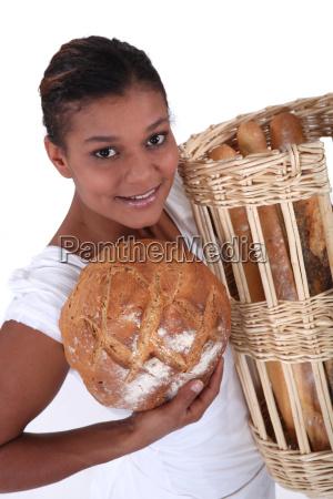 female baker holding bread studio shot