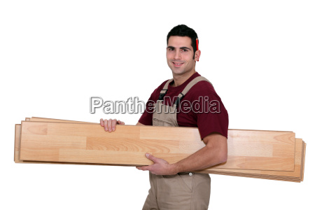 worker carrying wooden planks