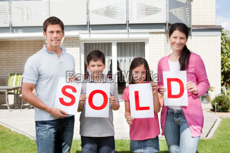 familie haelt ein schild verkauft ausserhalb