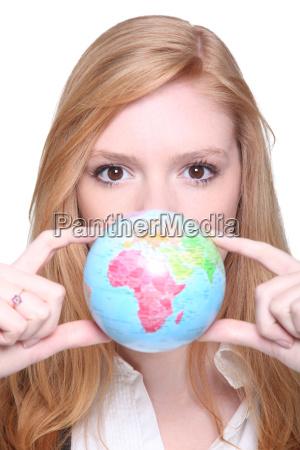 junge frau zeigt einen kleinen globus