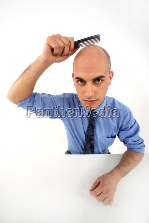 bald man holding comb