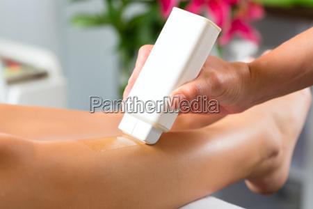 frau in kosmetikstudio enthaart die beine