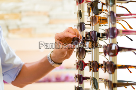 young man at the optician buys
