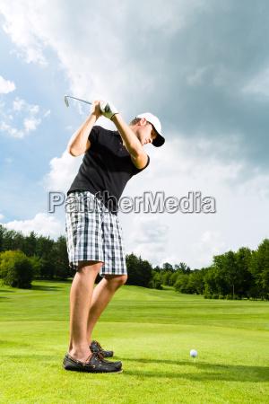 junger golf spieler am golfplatz beim