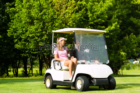 young sportive couple with golf cart