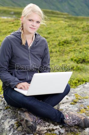 junge blonde frau mit laptop auf