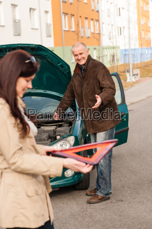 woman holding triangle sign repairman fixing