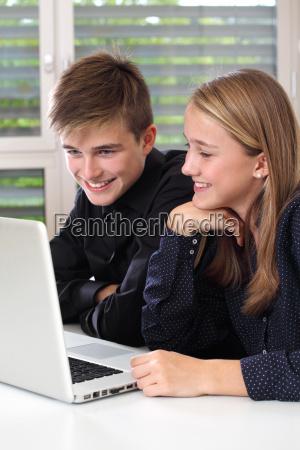 glueckliche studenten die an einem laptop