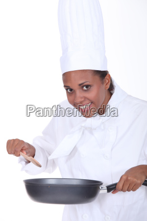 female chef stirring sauce