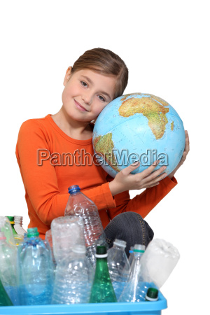 young girl hugging a globe behind