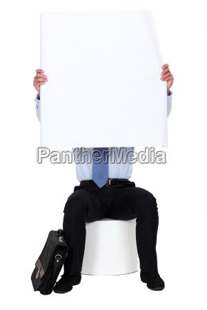 man sat on stool holding blank