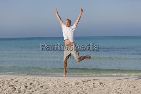 froehlicher mann springt lachend am strand