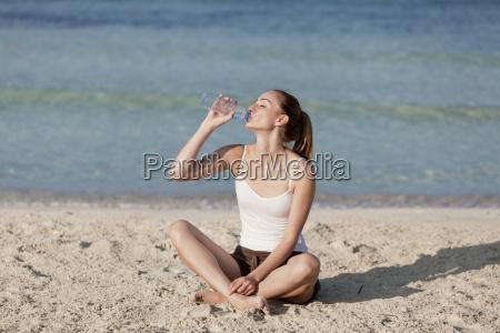 frau trinkt wasser aus einer flasche
