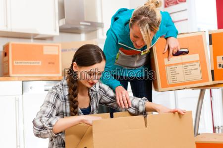 dwie kobiety z ruchomymi kartonami do