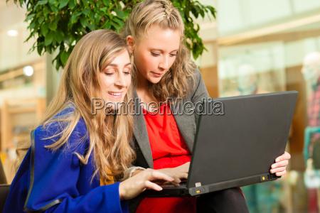 zwei freundinnen beim shoppen in einer