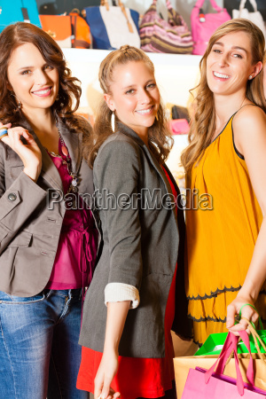 three girlfriends shopping in a mall