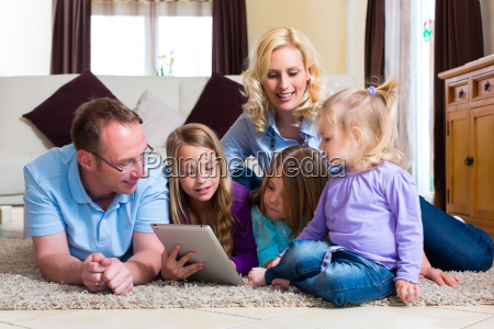 family playing with tablet computer at