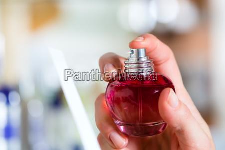 junge frau kauft parfum in parfuemerie