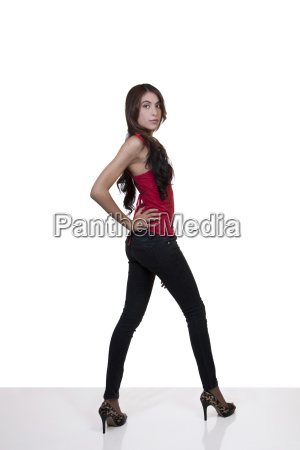 young hispanic woman standing jeans red