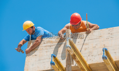 construction workers nailing cement formwork in
