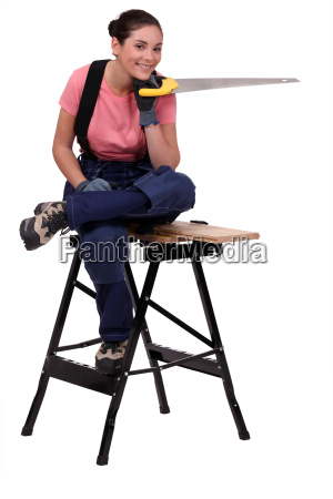 woman work on workbench holding saw