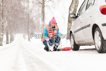 frau mit reifenketten auto schneesturz