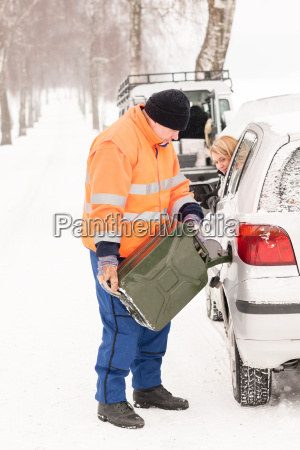 man filling woman car gas winter