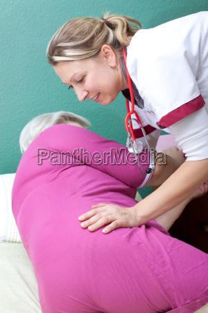 pflegerin hilft patientin beim aufstehen oder