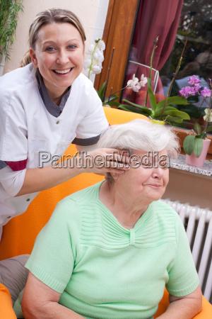 pflegerin massiert den kopf einer patientin