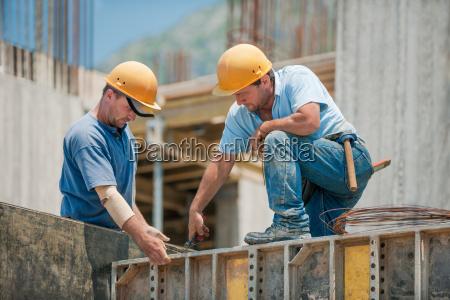 zwei bauarbeiter installieren betonschalungen rahmen
