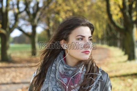 woman with earphones in park