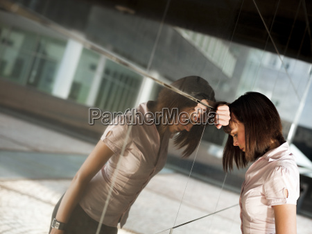 frustrated woman banging head against wall